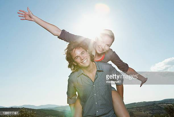 Italy, Tuscany, Young man carrying woman on his back against sun