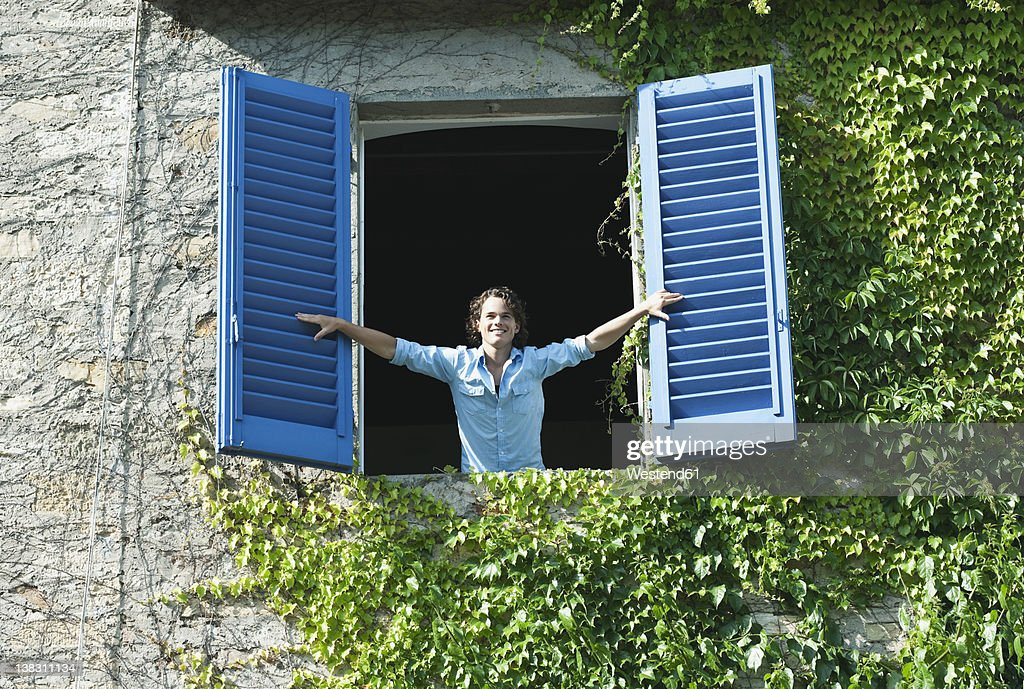 Italy, Tuscany, Young man leaning on window with shutters : Stock Photo