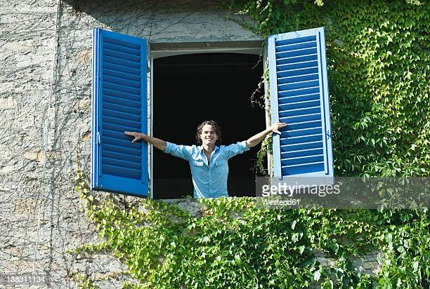 Italy, Tuscany, Young man leaning on window with shutters