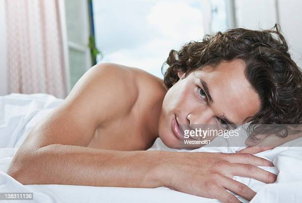 Italy, Tuscany, Young man lying on bed in hotel room, portrait
