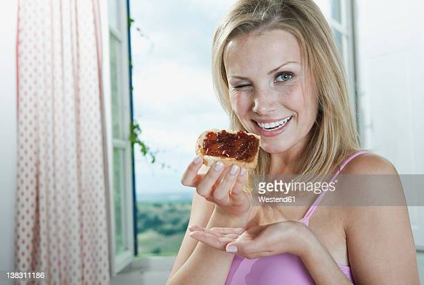Italy, Tuscany, Young woman holding bread and jam in hotel room, portrait, winking