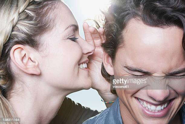 Italy, Tuscany, Young woman whispering in man's ear, close up