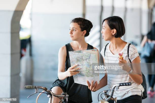 Italy, two young tourists with bicycles and map