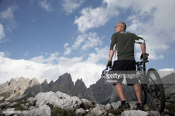 Italy, Tyrol, senior biker looking at view in mountains, low angle view, rear view