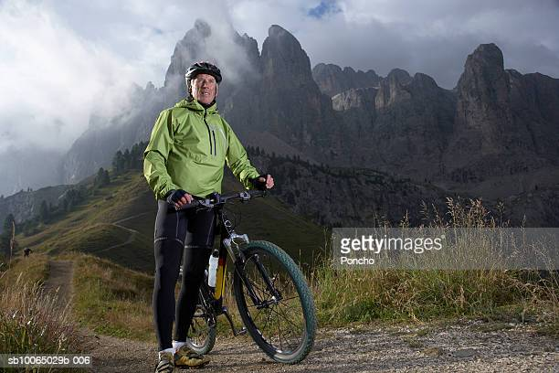Italy, Tyrol, senior biker standing with mountain bike on mountain ridge