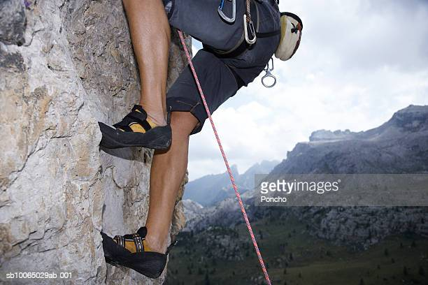 Italy, Tyrol, senior man rock climbing, low section