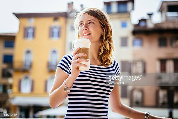Italy, Udine, portrait of smiling young woman with coffee to go