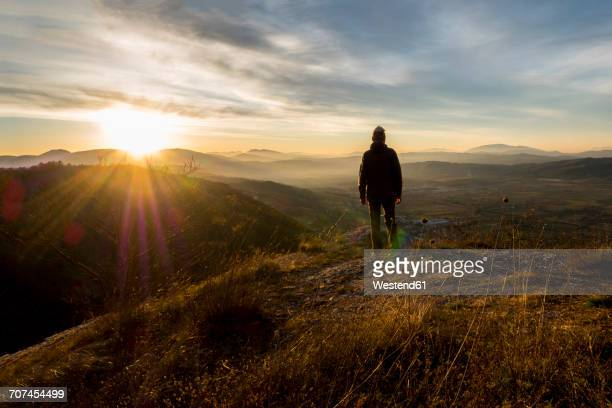 italy, umbria, gubbio, man watching sunrise on sibillini mountain range - sunrise contemplation stock pictures, royalty-free photos & images