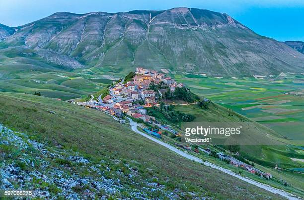 italy, umbria, monti sibillini national park, the small town of castelluccio di norcia and the vettore mountain at sunset - castelluccio stock photos and pictures