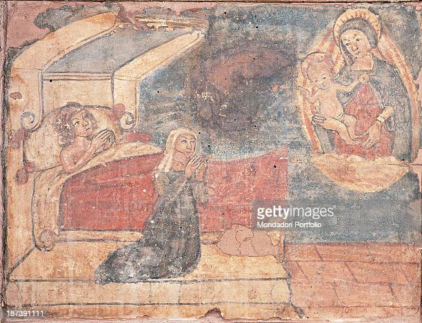 Italy Umbria Trevi Pinacoteca Civica All A woman kneeled down pleads Holy Mary with Christ child both suspended in midair on an cloud and surrounded...