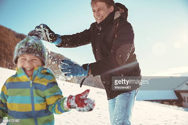 Italy, Val Venosta, Slingia, father and son having a snowball fight