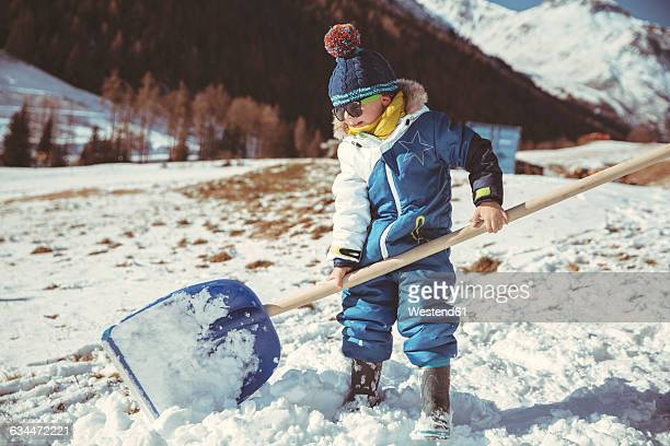 italy, val venosta, slingia, small boy using a large snow shovel - snow shovel stock photos and pictures