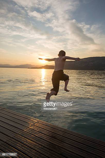 Italy, Veneto, Bardolino, Lake Garda, boy jumping into the water at sunset