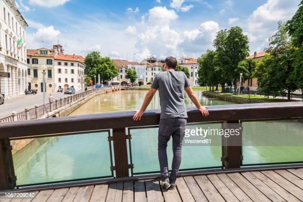 italy, veneto, treviso, tourist looking on river - garde corps photos et images de collection