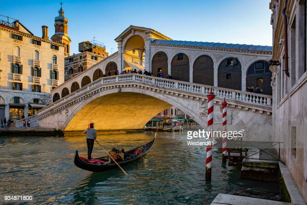 italy, veneto, venice, gondola on canal grande in front of rialto bridge - venise photos et images de collection
