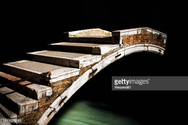 italy, veneto, venice, old arch bridge stretching over dark city canal - venice italy stock pictures, royalty-free photos & images