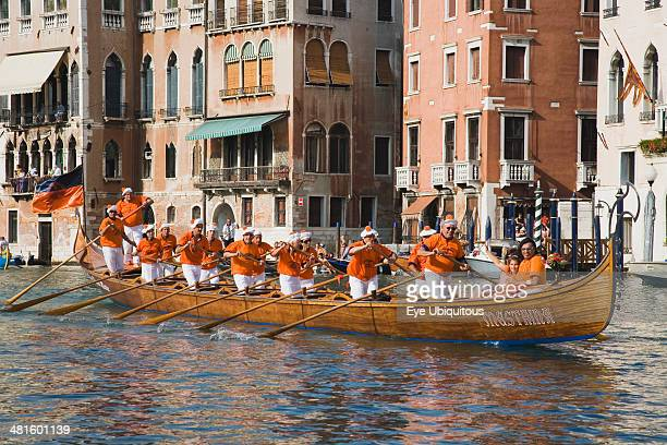 Italy Veneto Venice Regatta Storico historical annual regatta Team of rowers wearing orange and white costume passing canal side buildings with...