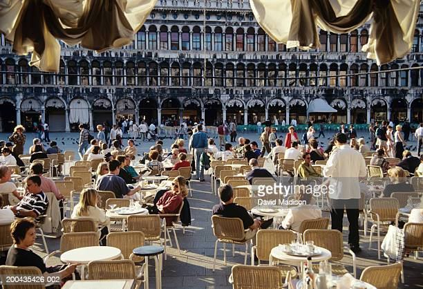 italy, veneto, venice, st. mark's square, people sitting at cafe - italian culture stock pictures, royalty-free photos & images