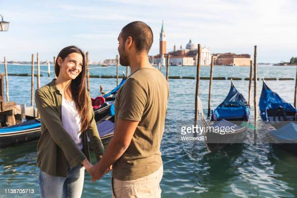 italy, venice, affectionate young couple with gondola boats in background - gondola traditional boat stock pictures, royalty-free photos & images