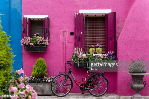 bike in front of a pink house in Burano