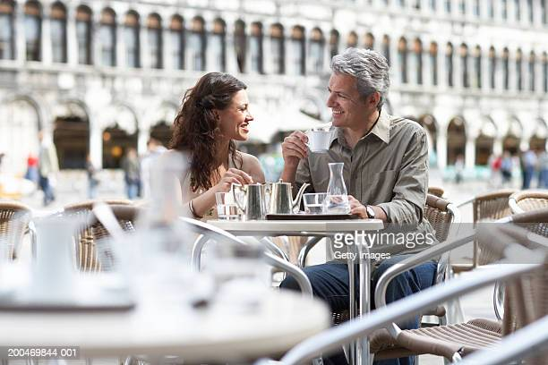 italy, venice, couple at cafe table, outdoors, smiling at each other - pavement cafe stock pictures, royalty-free photos & images