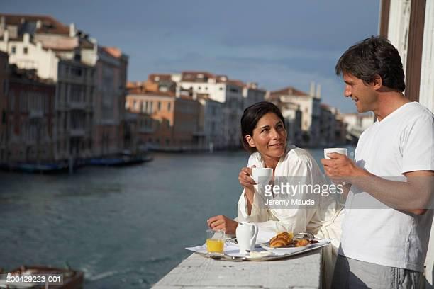 Italy, Venice, couple having breakfast on balcony by canal, smiling