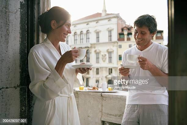 Italy, Venice, couple having  coffee on balcony, smiling