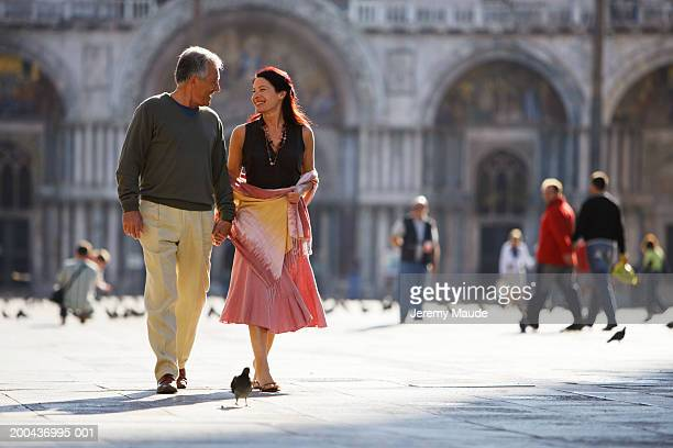 Italy, Venice, couple holding hands walking in square, smiling