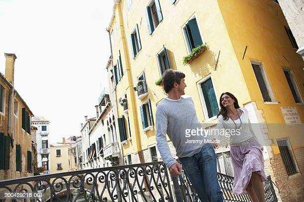 italy, venice, couple holding hands walking over canal bridge, smiling - mid adult women stock pictures, royalty-free photos & images