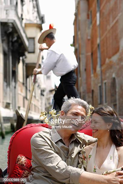 Italy, Venice, couple in gondola, man's arms around woman, smiling