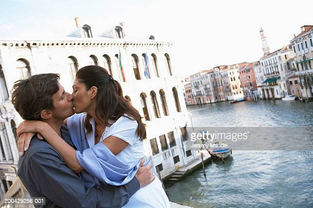 italy, venice, couple kissing on canal bridge - heterosexuelles paar stock-fotos und bilder