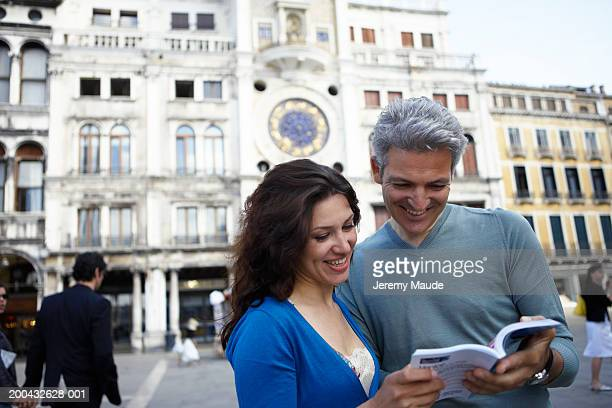 Italy, Venice, couple reading guide book in St Mark's Square