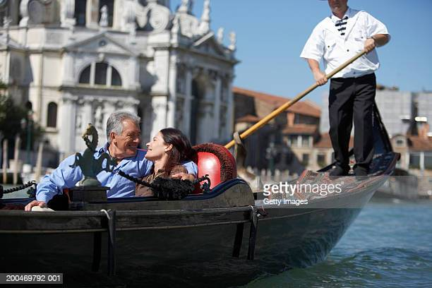 'Italy, Venice, couple riding in godola, smiling at each other'