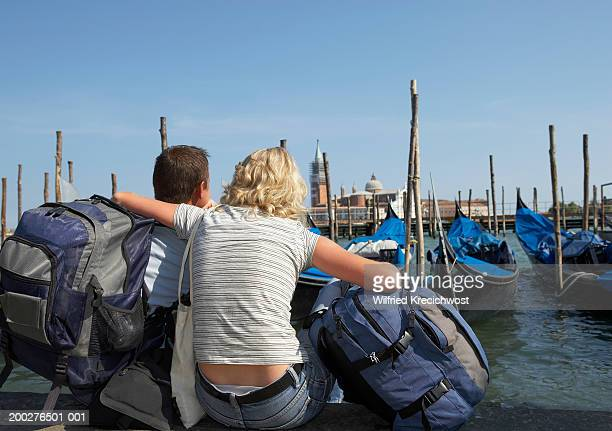italy, venice, couple sitting by canal holding rucksacks, rear view - 半そで ストックフォトと画像
