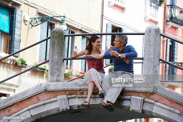 italy, venice, couple sitting on bridge holding ice cream cones - europe stock pictures, royalty-free photos & images