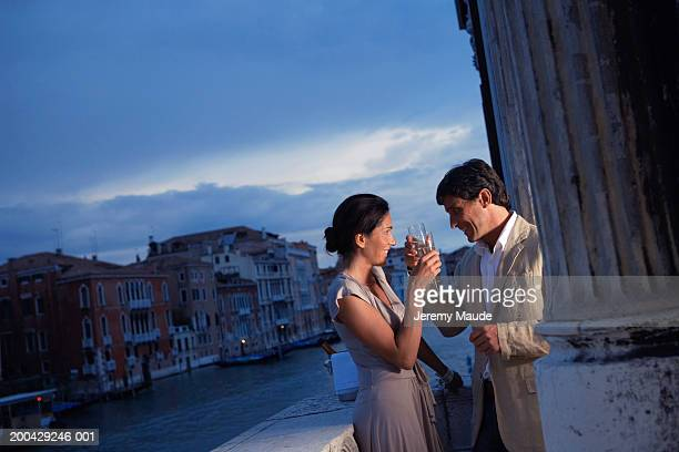 Italy, Venice, couple toasting drinks on balcony, smiling, dusk
