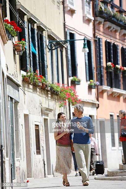 Italy, Venice, couple walking in street holding ice cream cones