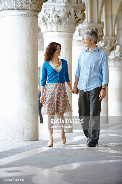 Italy, Venice, couple walking through colonnade, holding hands