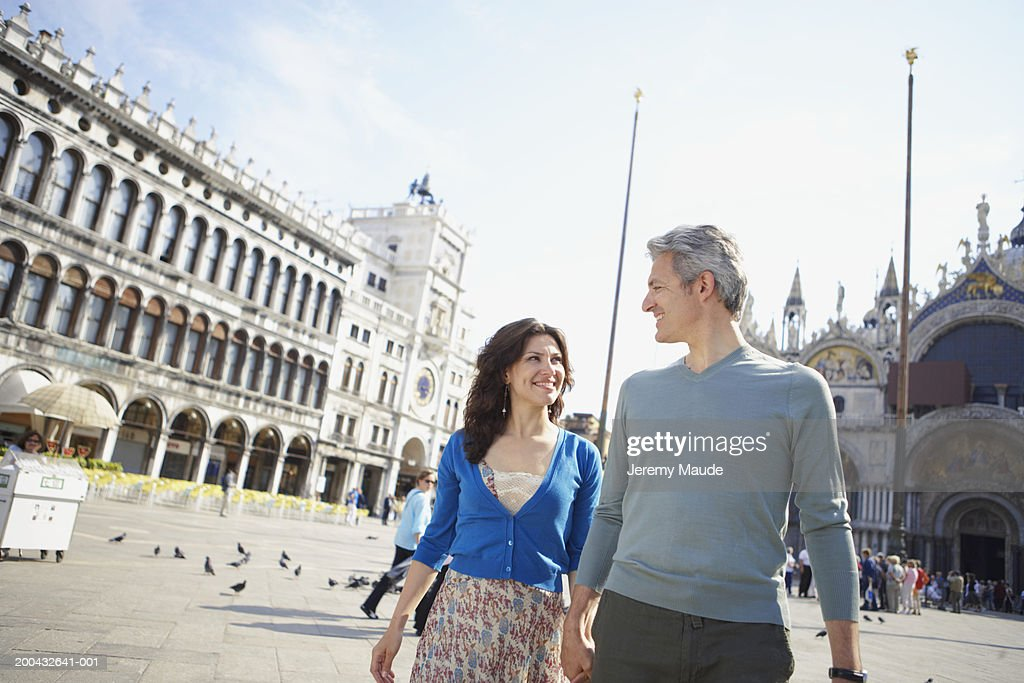Italy, Venice, couple walking through St Mark's Square, holding hands : Stock Photo