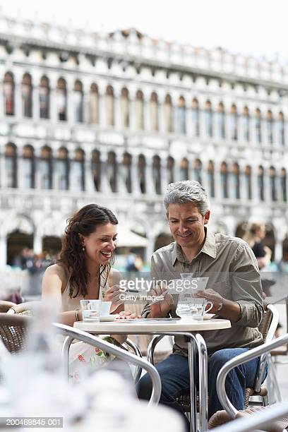 Italy, Venice, couple writing postcards at cafe table, outdoors