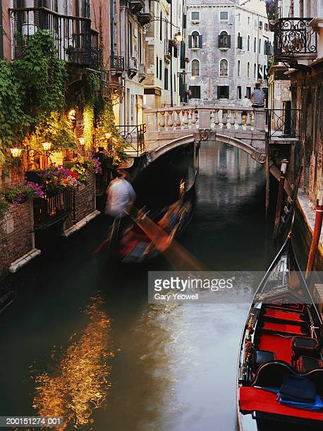 italy, venice, gondola (blurred motion) on canal - yeowell stock photos and pictures