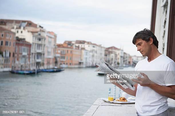 Italy, Venice, man reading newspaper on balcony by breakfast tray