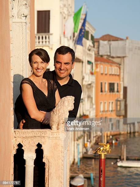 Italy, Venice, Mature couple embracing on balcony over canal