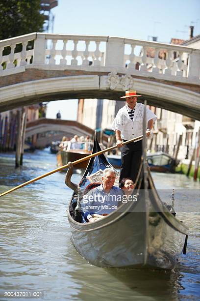 Italy, Venice, mature couple in gondola on canal, smiling