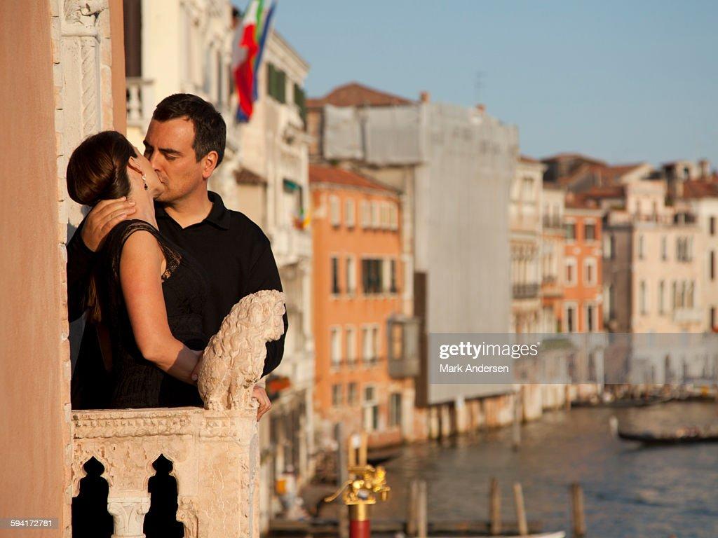 italy venice mature couple kissing on balcony over canal stock photo