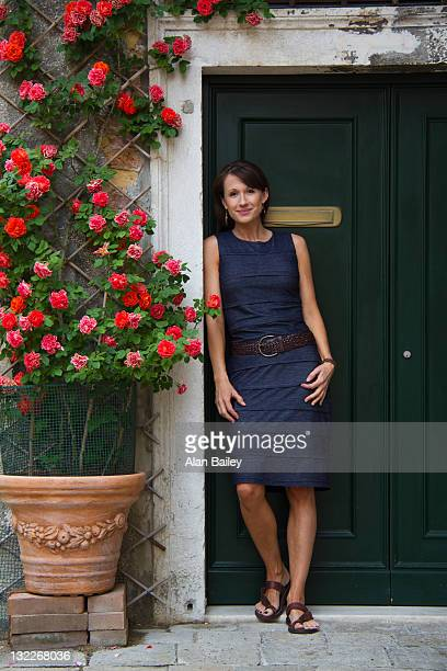 Italy, Venice, Mature woman standing against old doors, potted red roses on side