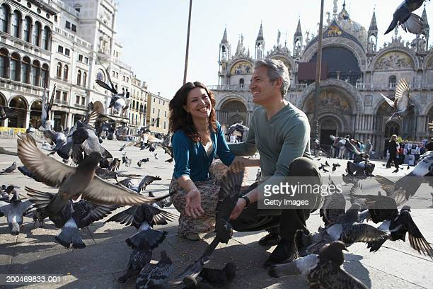 Italy, Venice, Piazza San Marco, couple crouching amongst pigeons