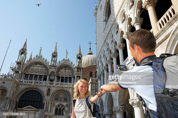 Italy, Venice, St Mark's Square, couple reaching towards each other