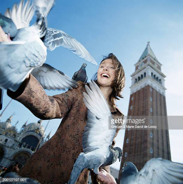 Italy, Venice, St Marks Square, woman feeding pigeons, low angle view
