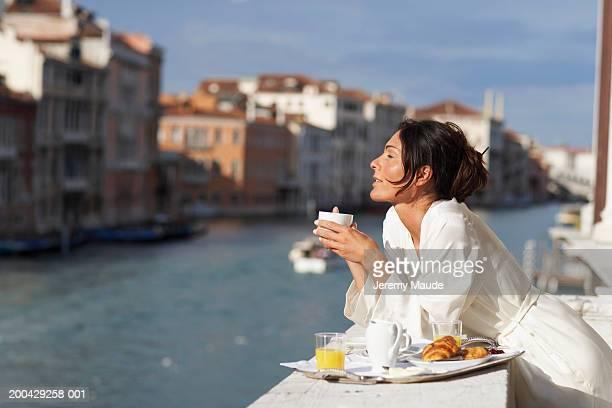 Italy, Venice, woman having breakfast on balcony, eyes closed, smiling